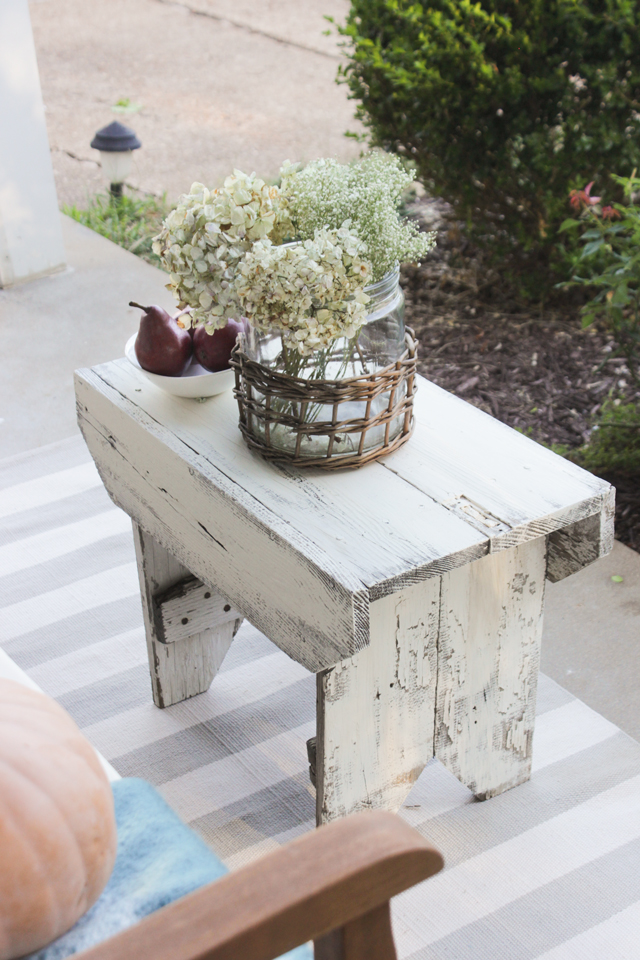 Chippy wooden stool as a table on a fall front porch