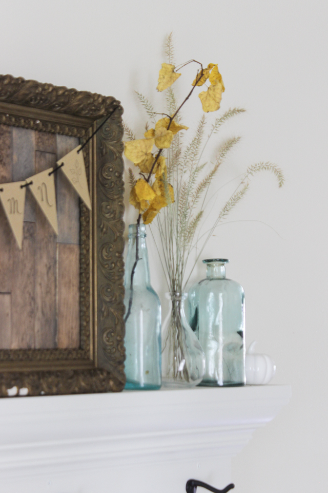 Fall shelf vignette with aqua bottles, yellow fall leaves, and wheat
