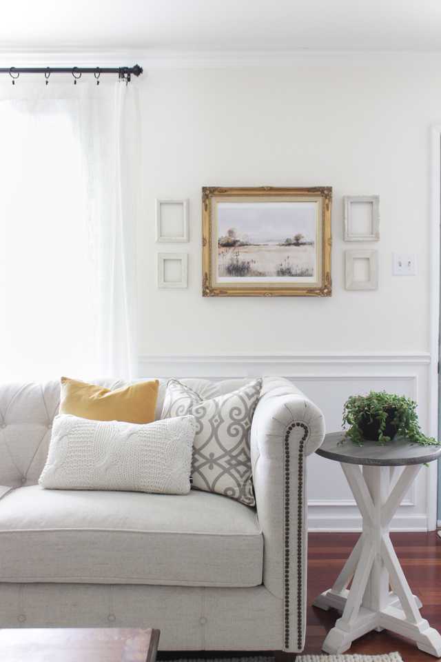 Fall living room with tufted couch, fall watercolor painting, and trestle end table