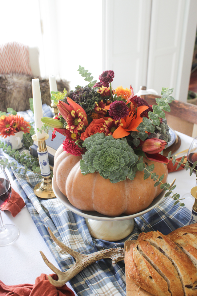 A colorful Thanksgiving Tablescape with a pumpkin floral centerpiece