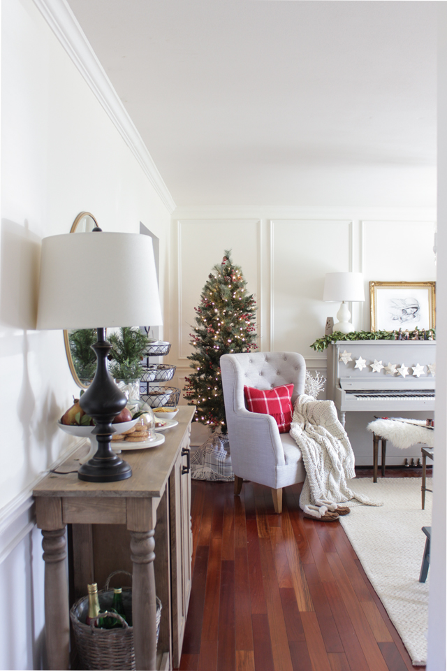 Small Christmas tree tucked in corner behind a wing chair