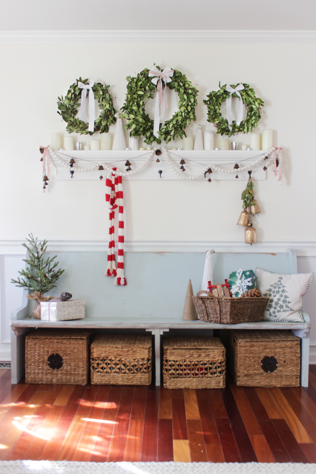 Christmas entry bench with three bay leaf wreaths above