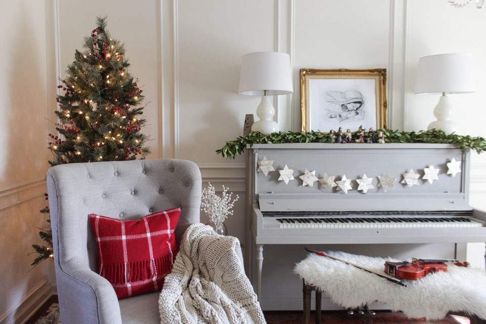 Corner Christmas tree, wing chair, and gray piano with garland