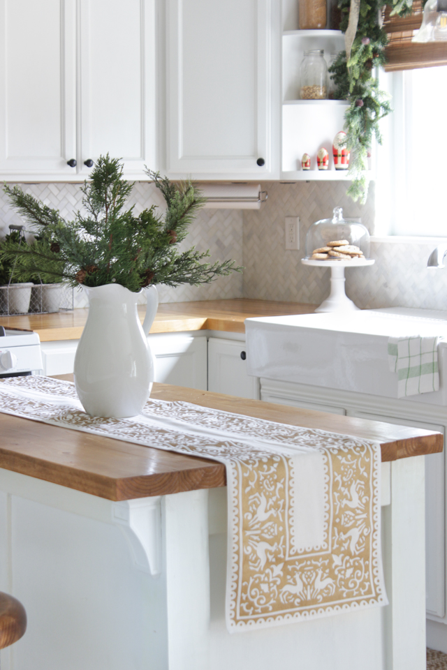 Table runner on kitchen island with Christmas greens in a vase