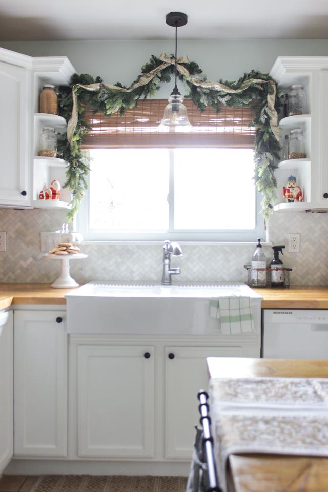 Pretty faux garland draped above a farmhouse kitchen sink