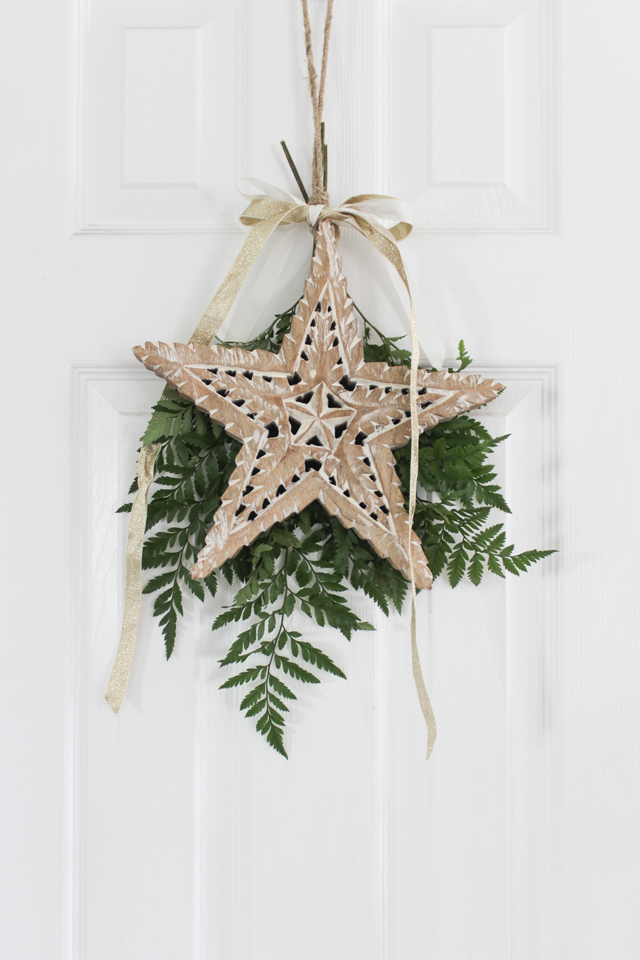 Christmas wooden star and fresh greens hanging on interior door