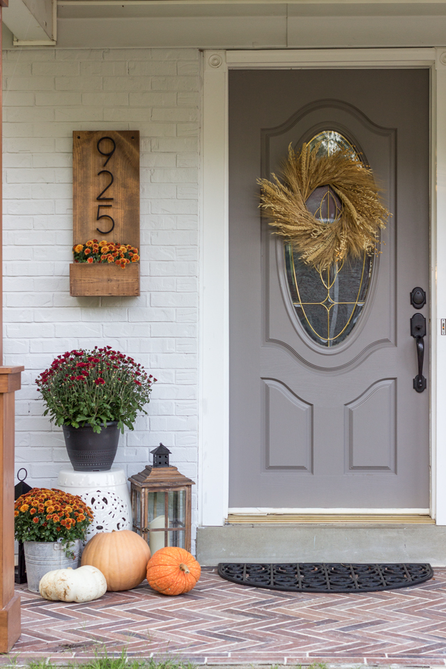 Fall front door dressed up with pumpkins, mums, and lanterns