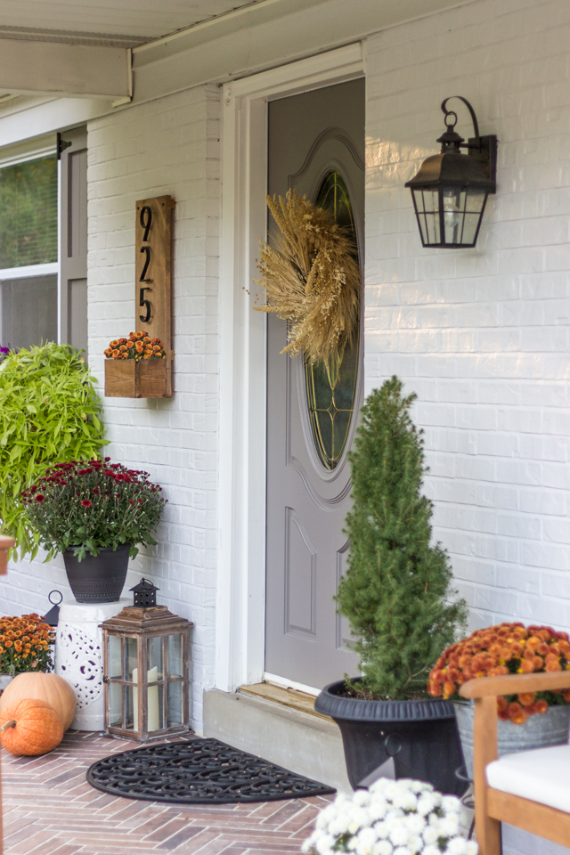 Fall front door with mums, pumpkins and lanterns.