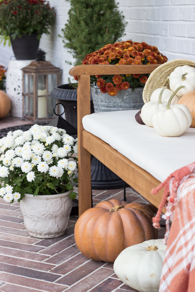 Pumpkins and mums surround a wooden bench on fall front porch