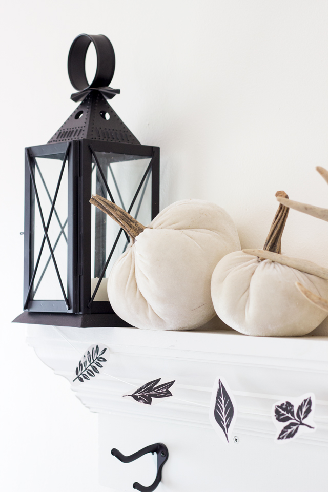 Black lantern, velvet white pumpkins, and leaf garland on fall mantel