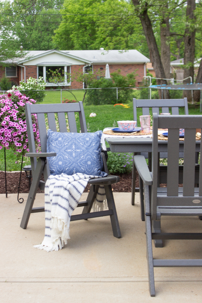 Navy pillow, striped throw, gray outdoor dining furniture