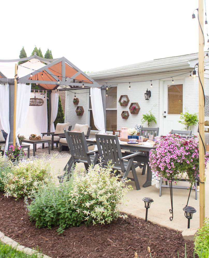 White painted brick, pergola, and gray outdoor furniture